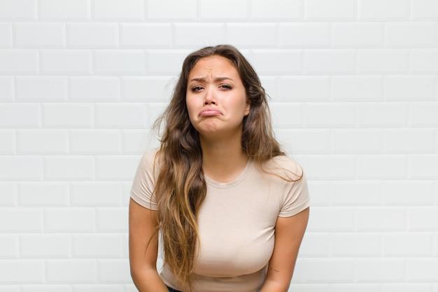 Mujer bonita joven contra la pared blanca