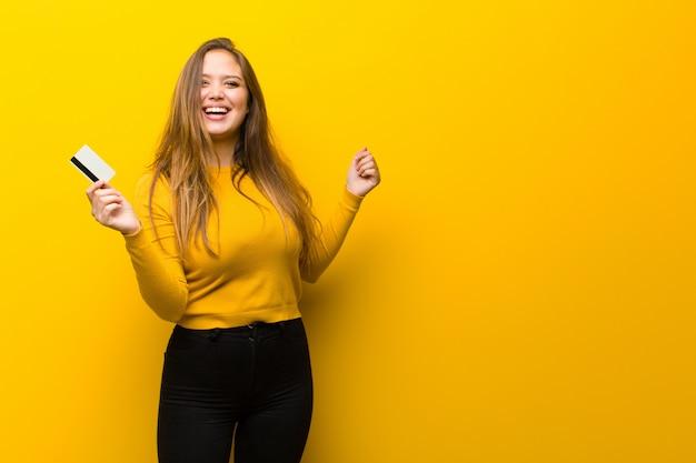 Mujer bonita joven dinero o concepto de compras contra la pared amarilla