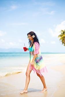 Mujer bonita joven divirtiéndose en la playa, traje tropical boho brillante y bikini. beber un sabroso cóctel, vacaciones de lujo cerca del océano azul claro.