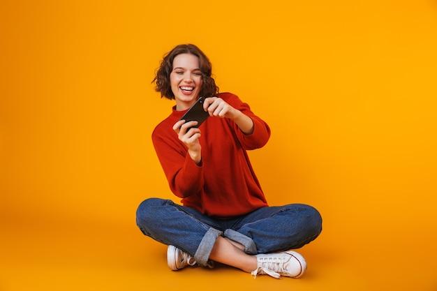 Mujer bonita joven emocional posando aislada en la pared amarilla usando juegos de teléfono móvil.