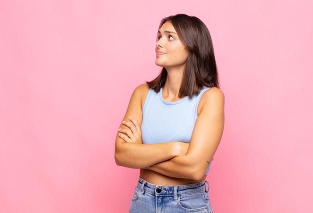Mujer bonita joven encogiéndose de hombros, sintiéndose confundida e insegura