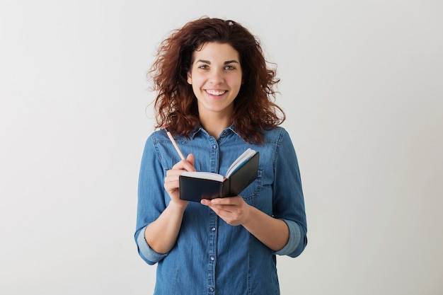 Mujer bonita joven escribiendo en un cuaderno con lápiz, sonriendo, cabello rizado, camisa azul denim positiva, feliz, aislada, estilo hipster, aprendizaje estudiantil, mirando a puerta cerrada, haciendo notas, educación
