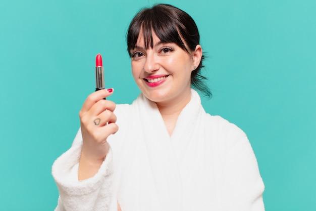 Mujer bonita joven con expresión feliz albornoz y sosteniendo un lápiz labial