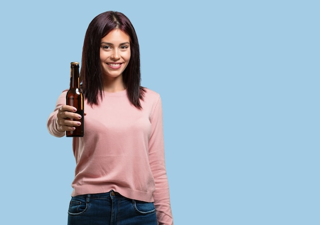 Mujer bonita joven feliz y divertida, sosteniendo una botella de cerveza