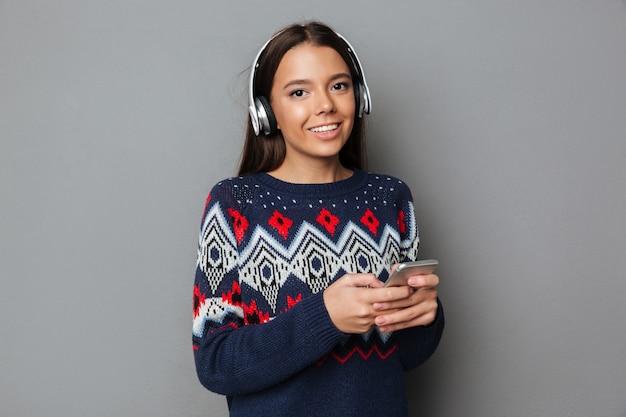 Mujer bonita joven feliz escuchando música y chateando por teléfono.