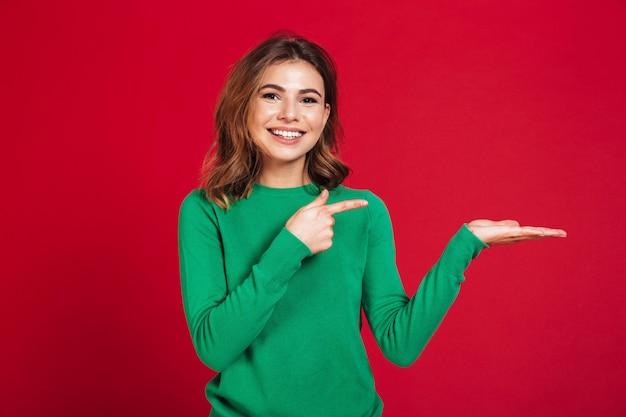 Mujer bonita joven feliz que muestra señalar del copyspace.
