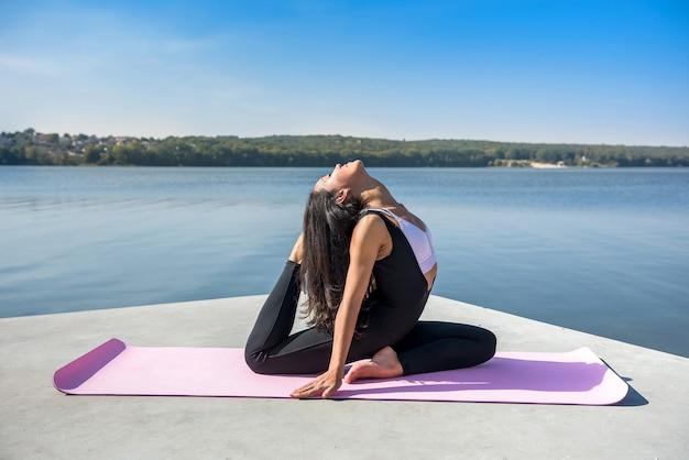 Mujer bonita joven fitness haciendo posturas de yoga, estirando en la naturaleza. estilo de vida saludable