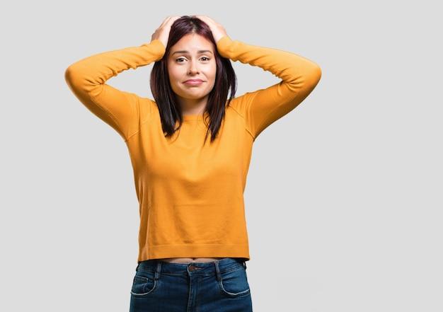 Mujer bonita joven frustrada y desesperada, enojada y triste con las manos en la cabeza