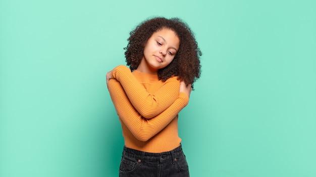 Mujer bonita joven gesticulando en la pared de color