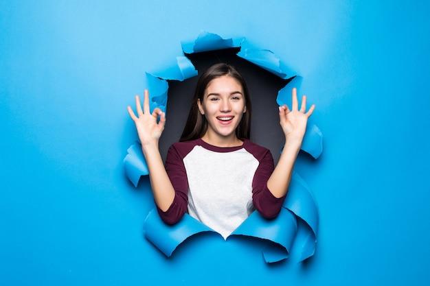 Mujer bonita joven con gesto aceptable mientras mira a través del agujero azul en la pared de papel.