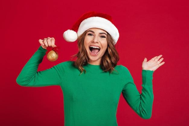 La mujer bonita joven de griterío que sostiene el árbol de navidad juega decoraciones.