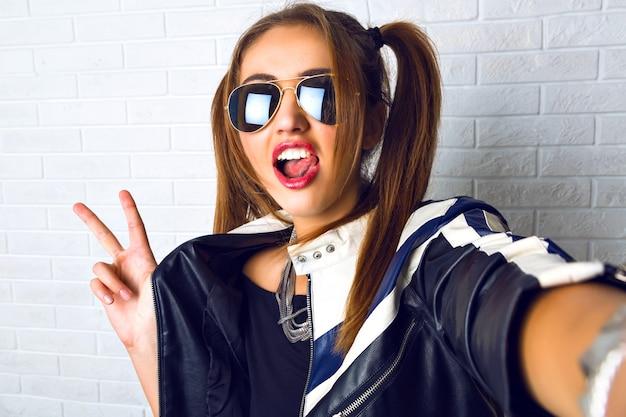 Mujer bonita joven haciendo selfie, maquillaje brillante, estuche hermoso, dos colas de caballo lindas, chaqueta de cuero de motociclista, pared de grunge urbano. divirtiéndose sola, haciendo fotos para sus amigos.