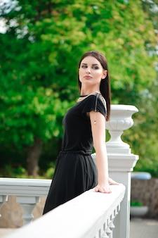 Mujer bonita joven hermosa que se relaja en el balcón.