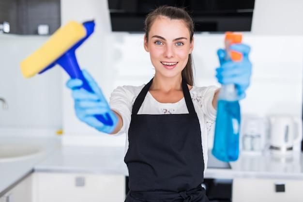 Mujer bonita joven hoding herramientas limpias de pie en la cocina