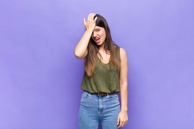 Mujer bonita joven levantando la palma hacia la frente