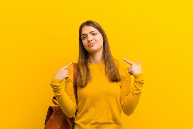 Mujer bonita joven con una mala actitud que parece orgullosa y agresiva, apuntando hacia arriba o burlándose de firmar con las manos sobre fondo naranja