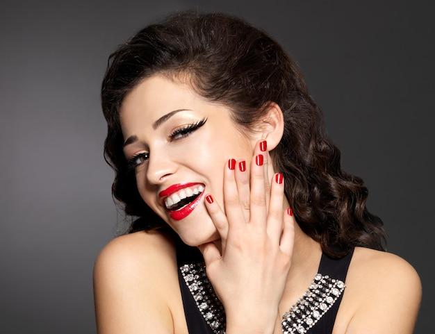 Mujer bonita joven con manicura roja y labios. modelo de moda con brillantes emociones positivas.