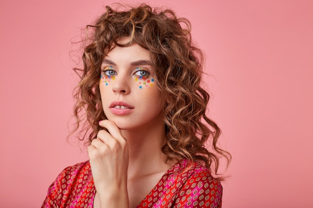 Mujer bonita joven manteniendo la mano debajo de la barbilla, vistiendo ropa a rayas de color rosa y naranja, mirando tranquilo