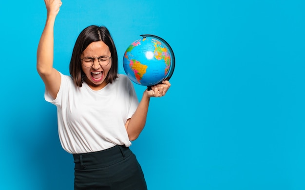 Mujer bonita joven con un mapa del mundo
