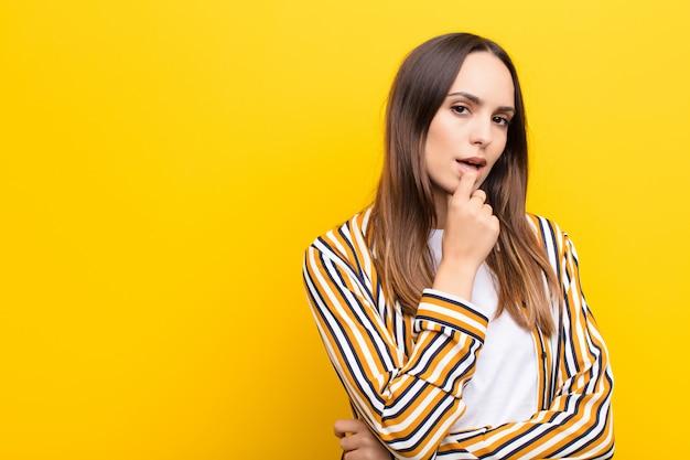 Mujer bonita joven con mirada sorprendida, nerviosa, preocupada o asustada, mirando hacia el lado hacia el espacio de la copia contra la pared naranja