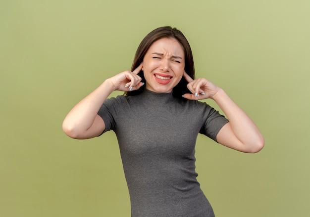Mujer bonita joven molesta poniendo los dedos en los oídos con los ojos cerrados aislado sobre fondo verde oliva