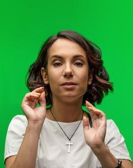 Mujer bonita joven con las palmas abiertas posando en chromakey.