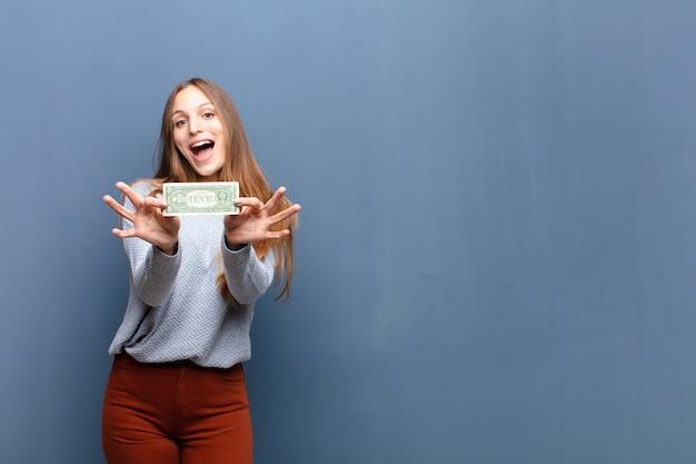 Mujer bonita joven con pared azul de billetes de dólar con un espacio de copia