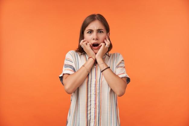 Mujer bonita joven con pelo corto tocando su rostro con ambas manos, con la boca abierta.