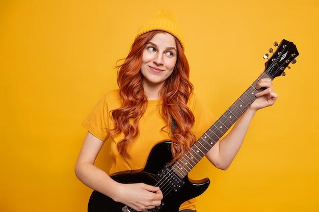 Mujer bonita joven con el pelo rojo disfruta de tocar la guitarra acústica tiene expresión complacida de ensueño