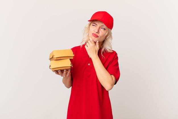 Mujer bonita joven pensando, sintiéndose dudoso y confundido. concepto de entrega de hamburguesas