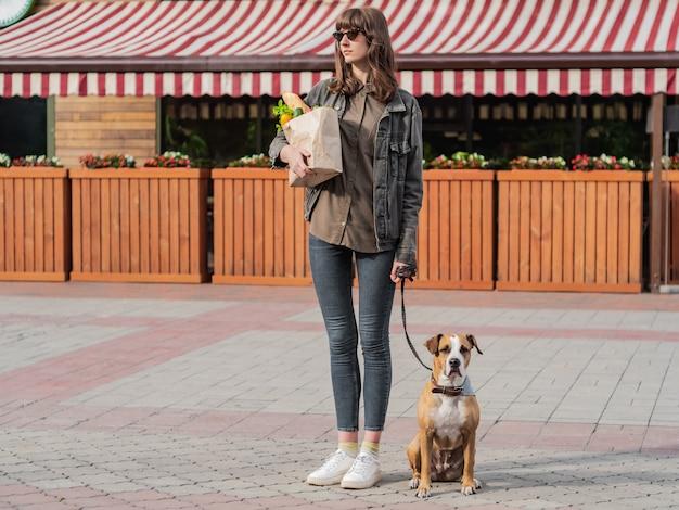 La mujer bonita joven con el perro sostiene la bolsa de papel de comestibles delante del mercado o de la tienda de verdura. ir a comprar comida con un cachorro pitbull terrier entrenado