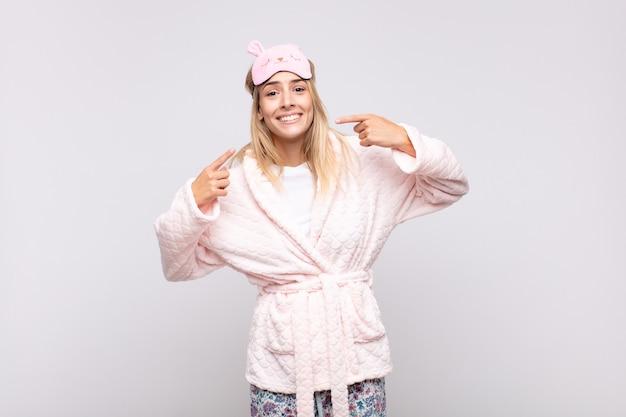 Mujer bonita joven en pijama, sonriendo con confianza apuntando a su propia sonrisa amplia, actitud positiva, relajada y satisfecha