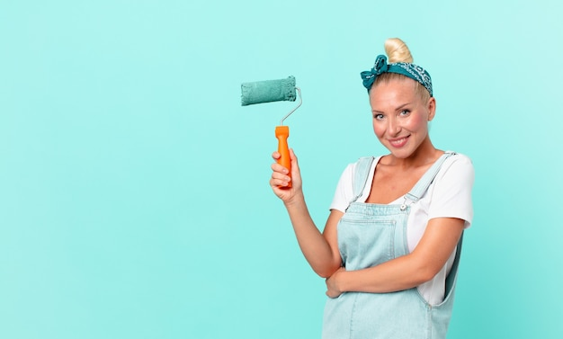 Mujer bonita joven pintando una pared con un rodillo