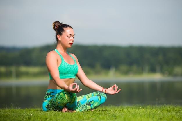 Mujer bonita joven en posición de loto en el parque