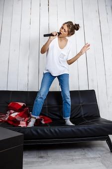 Mujer bonita joven que canta en micrófono en el sofá en casa.