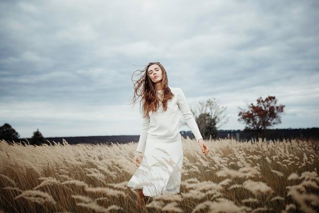 Mujer bonita joven que se coloca en el campo con trigo