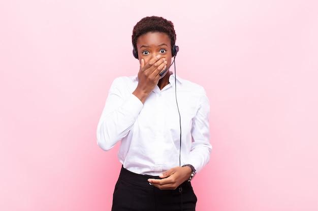 Mujer bonita joven que cubre la boca con las manos con una expresión de sorpresa, sorpresa, guardar un secreto o decir ¡uy!