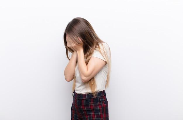 Mujer bonita joven que cubre los ojos con las manos con una mirada triste y frustrada de desesperación, llorando