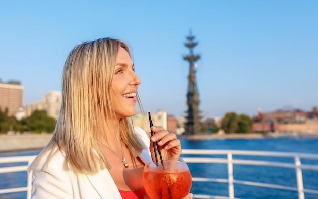 Mujer bonita joven que disfruta de la vista en la cubierta del crucero