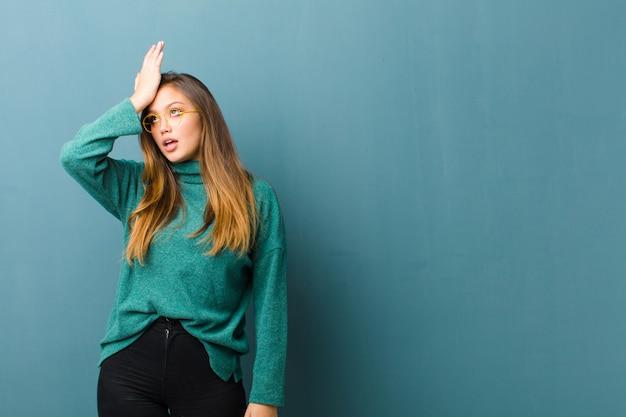 Mujer bonita joven que levanta la palma de la mano a la frente pensando uy, después de cometer un error estúpido o recordar, sentirse tonto