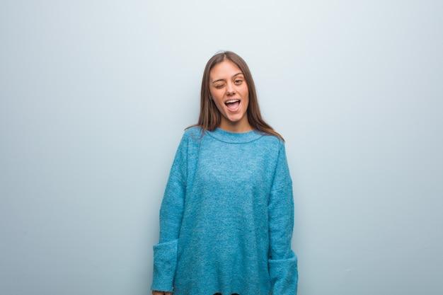 Mujer bonita joven que lleva un suéter azul que guiña, gesto divertido, amistoso y despreocupado