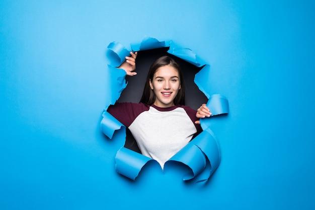 Mujer bonita joven que mira a través del agujero azul en la pared de papel.