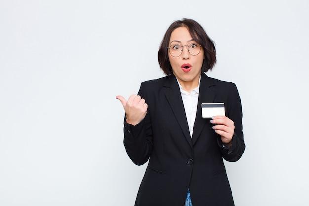 Mujer bonita joven que parece asombrada con incredulidad, apuntando al objeto a un lado y diciendo wow, increíble con una tarjeta de crédito