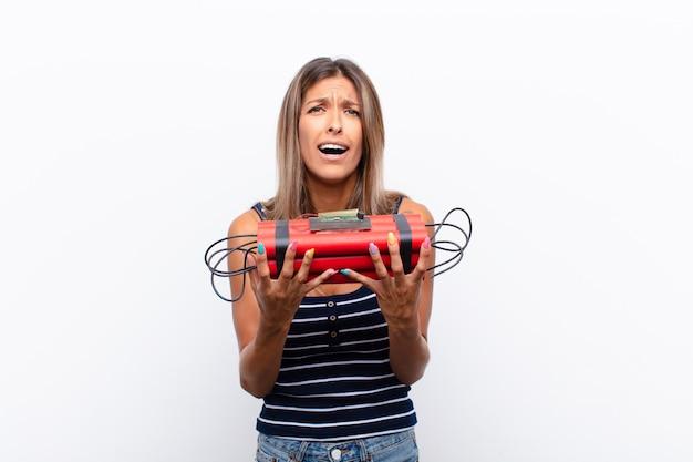 Mujer bonita joven que parece desesperada y frustrada, estresada, infeliz y molesta, gritando y gritando con una bomba de dinamita