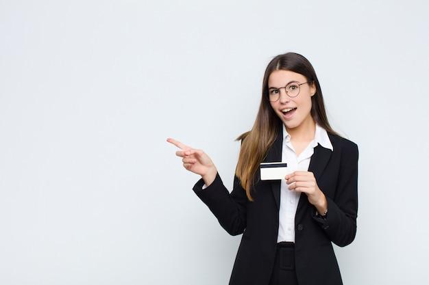 Mujer bonita joven que parece excitada y sorprendida apuntando hacia un lado y hacia arriba para copiar espacio con una tarjeta de crédito