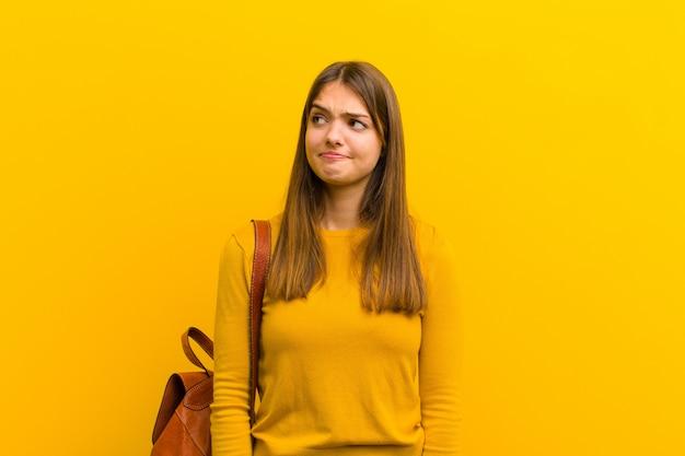 Mujer bonita joven que parece perpleja y confundida, preguntándose o tratando de resolver un problema o pensando contra el fondo naranja