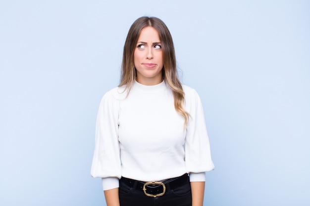 Mujer bonita joven que parece perpleja y confundida, preguntándose o tratando de resolver un problema o pensando contra la pared azul