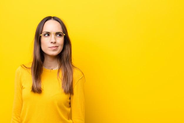 Mujer bonita joven que parece perpleja y confundida, preguntándose o tratando de resolver un problema o pensando contra la pared naranja