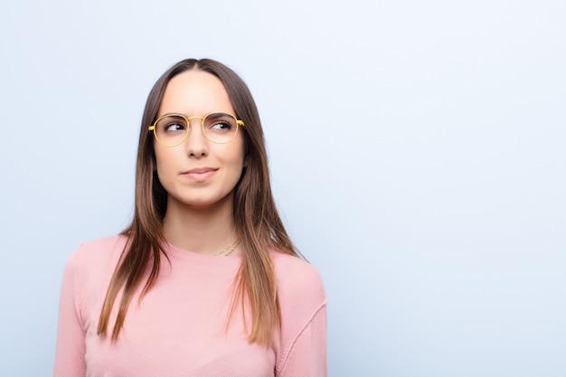 Mujer bonita joven que parece perpleja y confundida, preguntándose o tratando de resolver un problema o pensando sobre la pared azul