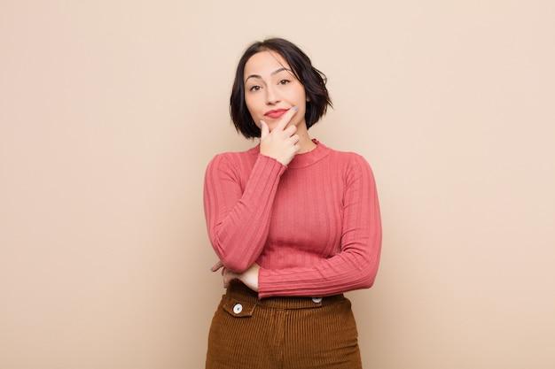 Mujer bonita joven que parece seria, reflexiva y desconfiada, con un brazo cruzado y la mano en la barbilla, opciones de ponderación sobre la pared beige